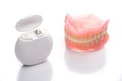 Modèle de dents avec le fil dentaire sur le fond blanc Photo stock