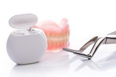 Modèle de dents avec le fil dentaire sur le fond blanc Photos stock