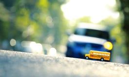 Modèle de jouet d'autobus scolaire sur la route Images stock
