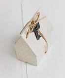 Modèle de maison de carton avec un arc de ficelle et de clé construction de logements, prêt, immobiliers ou achat d'un nouveau co Photographie stock libre de droits