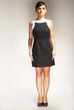 Modèle de mode sur le fond clair dans la robe noire Photographie stock libre de droits