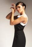 Modèle de mode sur le fond clair dans la robe noire Image stock