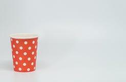 Modèle de point blanc sur la tasse de papier rouge avec le fond blanc et le foyer sélectif Photo libre de droits