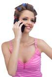 Modèle de sourire avec les rouleaux de port de cheveux de téléphone Images stock