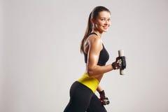Modèle de sourire femelle de forme physique avec des haltères Photographie stock libre de droits