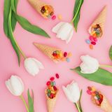 Modèle de sucrerie lumineuse colorée en cônes de gaufre et fleurs blanches sur le fond rose Configuration plate, vue supérieure Photographie stock