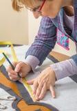 Modèle de tailleur de dessin de couturière sur la table Photos libres de droits