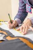 Modèle de tailleur de dessin de couturière sur la table Image stock