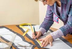 Modèle de tailleur de dessin de couturière sur la table Images stock