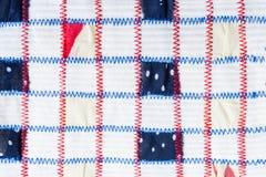 Modèle de textile des morceaux carrés de tissus colorés, cousus par les coutures rouges et bleues de zigzag sur le tissu blanc Photo libre de droits