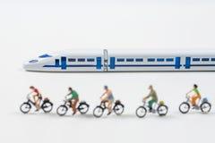 Modèle de train à grande vitesse et personnes miniatures montant un vélo Image libre de droits