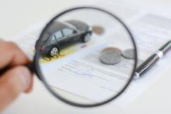 Modèle de voiture sous la loupe chez la main de la femme suggérant la recherche de voiture Images libres de droits