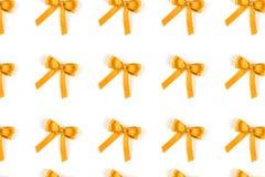Modèle des arcs en soie jaunes de cadeau d'isolement sur le blanc photos stock