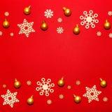 Modèle des flocons de neige en bois et des boules de nouvelle année d'or sur un Ba rouge Image libre de droits