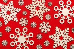 Modèle des flocons de neige en bois sur le fond rouge Photos libres de droits