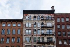 Modèle des sorties de secours et des dispositifs climatiques de fenêtre du côté du vieil immeuble de brique photographie stock