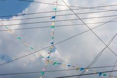 Modèle diagonal avec des lignes électriques et des drapeaux contre le ciel nuageux Photo stock