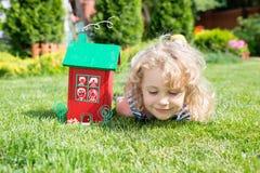 Modèle en bois de la maison et de la petite fille blonde se trouvant sur l'herbe Images libres de droits