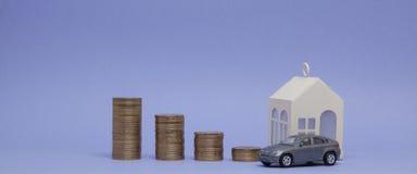 Modèle et maison gris de voiture avec des pièces de monnaie sous forme d'histogramme sur un fond pourpre Concept du prêt, l'éparg Images stock