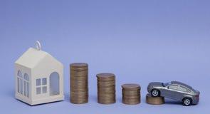 Modèle et maison gris de voiture avec des pièces de monnaie sous forme d'histogramme sur un fond pourpre Concept du prêt, l'éparg Image stock