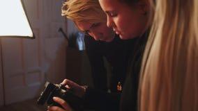 Modèle et photographe blonds de fille en photos de observation de studio de photo in camera, mode à l'arrière plan Photographie stock