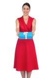 Modèle fascinant heureux dans le présent de offre de robe rouge Images libres de droits