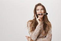 Modèle femelle attrayant avec les cheveux justes tenant la brosse de maquillage dans la bouche, la touchant avec le doigt tout en Photos stock