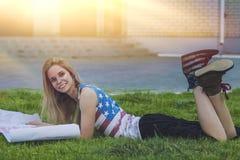 Modèle femelle contre une pelouse dans un T-shirt avec le drapeau américain Photo stock