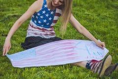 Modèle femelle contre une pelouse dans un T-shirt avec le drapeau américain Photos libres de droits