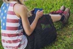 Modèle femelle contre une pelouse dans un T-shirt avec un drapeau américain a Photographie stock libre de droits