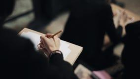 Modèle femelle de fille de dessin de main d'étudiant d'arts avec le crayon sur le livre blanc banque de vidéos