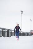 Modèle femelle de forme physique attrayante fonctionnant au parc d'hiver de neige, espadrilles roses Photo libre de droits