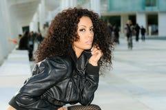 Modèle femelle noir à la mode se reposant sur un banc Image stock