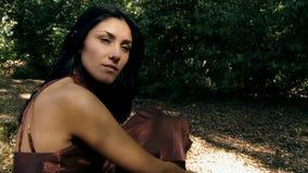 Modèle femelle renversant posant dans la forêt banque de vidéos