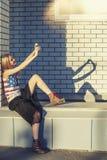 Modèle femelle sur le fond d'un bâtiment dans un T-shirt Photographie stock libre de droits