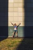 Modèle femelle sur le fond d'un bâtiment dans un T-shirt avec a Photographie stock