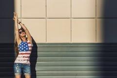 Modèle femelle sur le fond d'un bâtiment dans un T-shirt avec a Image stock