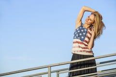 Modèle femelle sur le fond du ciel dans un T-shirt avec Amer Photographie stock libre de droits