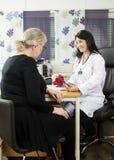 Modèle femelle To Senior Patient de docteur Explaining Rotator Cuff Photographie stock libre de droits