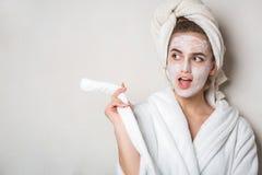Modèle Flirty de brune avec hydrater la serviette crème de masque et de bain sur la tête L'espace vide images stock