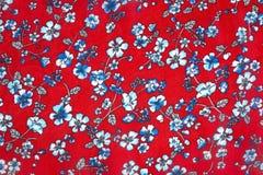 Modèle floral bleu sans couture à l'arrière-plan de couleur rouge sur le tissu photos stock