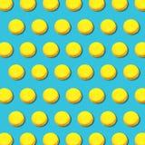 Modèle géométrique vibrant des macarons jaunes sur le fond de turquoise images stock