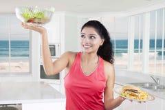 Modèle heureux avec les repas sains et malsains Photographie stock libre de droits
