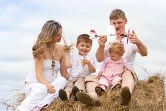 Modèle heureux d'aéronefs de jouet de famille sur la meule de foin Photo libre de droits