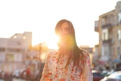 Modèle heureux de brune posant au fond de ville de tache floue avec des rayons du soleil L'espace pour le texte images libres de droits