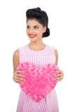Modèle joyeux de cheveux noirs tenant un oreiller en forme de coeur rose Photos stock