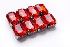 Modèle lâche rouge de pierres gemmes sur le fond blanc Photo stock