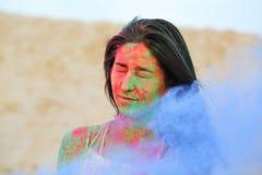 Modèle magnifique de brune posant avec éclater la poudre sèche bleue de Holi au désert images libres de droits