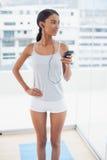 Modèle magnifique réfléchi dans les vêtements de sport écoutant la musique Photographie stock