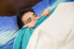 Modèle masculin beau seul se trouvant sur son lit Photo libre de droits